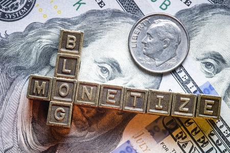 letter blocks: monetize blog phrase made from metallic letter blocks over dollar banknotes Stock Photo