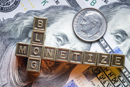 monetize: monetize blog phrase made from metallic letter blocks over dollar banknotes Stock Photo