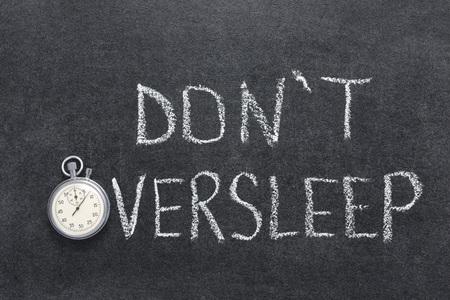 oversleep: don't oversleep phrase handwritten on chalkboard with vintage precise stopwatch used instead of O