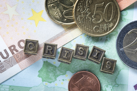 in europe: crisis word made from metallic letter blocks over euro banknotes and coins