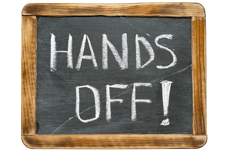 hands off: hands off exclamation  handwritten on vintage school slate board isolated on white Foto de archivo