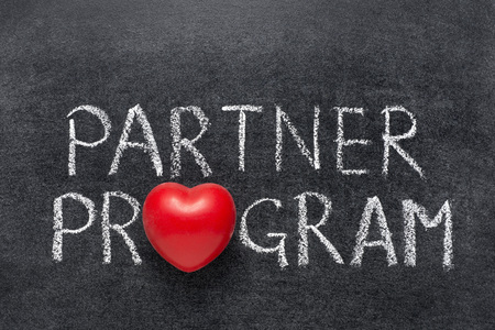 uniting: partner program phrase handwritten on blackboard with heart symbol instead of O Stock Photo