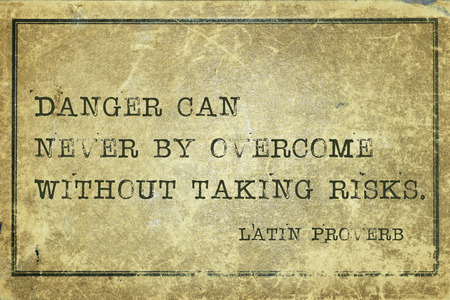 proverb: Danger can never by overcome - ancient Latin proverb printed on grunge vintage cardboard