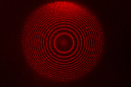 coherence: interference pattern of real He-Ne gas laser light passed through etalon Fabry-Perot, image has typical speckle structure as feature of laser radiation Stock Photo