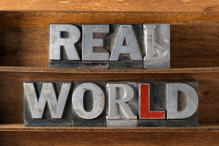 real world: real world phrase made from metallic letterpress type on wooden tray Stock Photo