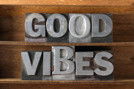 good wishes: good vibes phrase made from metallic letterpress type on wooden tray Stock Photo