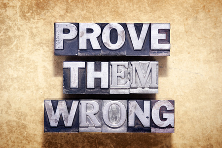 them: prove them wrong phrase made from metallic letterpress type on grunge cardboard background Stock Photo