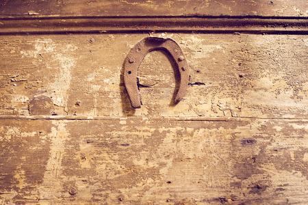 nailed: vintage rusty horseshoe nailed at the wooden wall