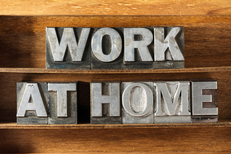 work from home: work at home phrase made from metallic letterpress type on wooden tray