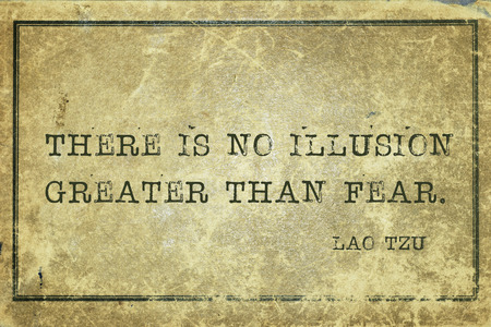 yellowish green: There is no illusion greater than fear - ancient Chinese philosopher Lao Tzu quote printed on grunge vintage cardboard Stock Photo