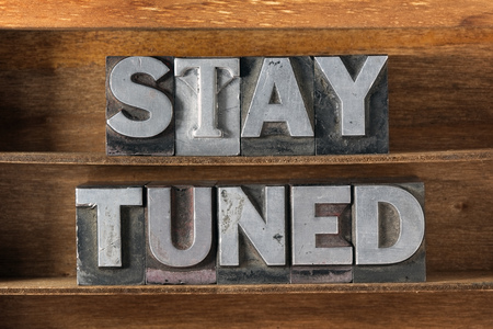 stay tuned phrase made from metallic letterpress type on wooden tray Stockfoto