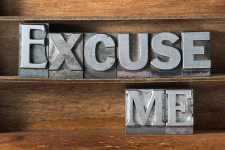excuse: excuse me phrase made from metallic letterpress type on wooden tray
