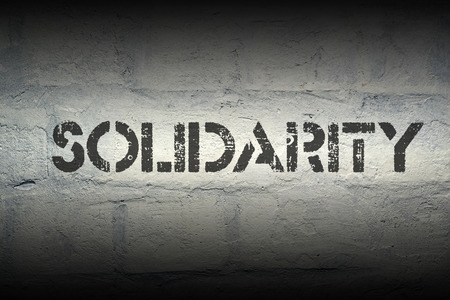 solidarity: solidarity stencil print on the grunge white brick wall