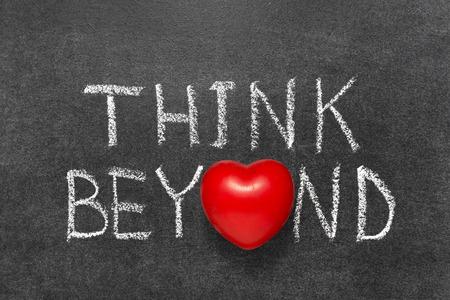 beyond: think beyond phrase handwritten on blackboard with heart symbol instead O