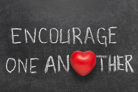 encourage one another phrase phrase handwritten on blackboard with heart symbol instead O