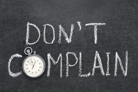 complain: dont complain phrase handwritten on chalkboard with vintage precise stopwatch used instead of O