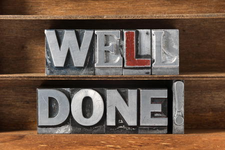 well made: well done exclamation phrase made from metallic letterpress type on wooden tray Stock Photo