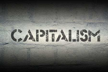 capitalismo: capitalismo palabra de la plantilla se imprime en la pared de ladrillo blanco grunge