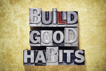 good habits: build good habits phrase made from metallic letterpress type on grunge cardboard background