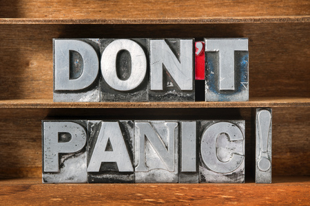 safety slogan: do not panic exclamation made from metallic letterpress type on wooden tray