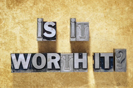 is it worth it question phrase made from metallic letterpress type on grunge cardboard background