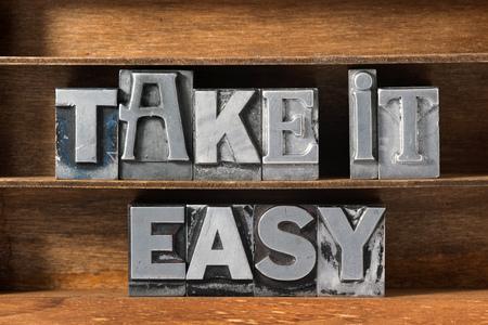 take it easy: take it easy phrase made from metallic letterpress type on wooden tray Stock Photo