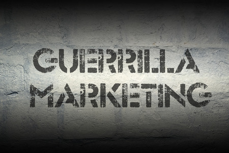 guerrilla: guerrilla marketing stencil print on the grunge white brick wall Stock Photo