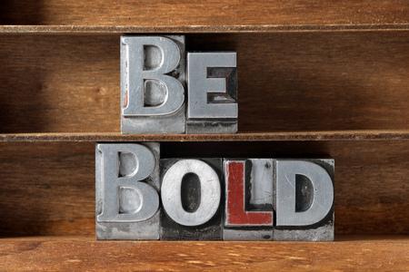 Sei mutiger Phrase aus metallischem Buchdruck Typ auf Holztablett