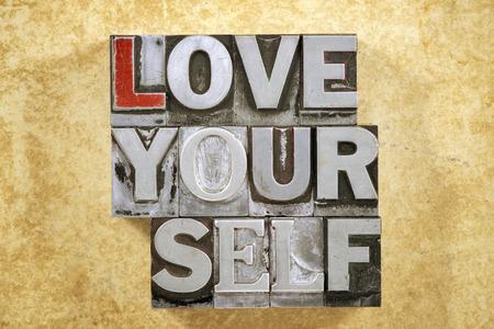 love yourself phrase made from metallic letterpress type on grunge cardboard background 版權商用圖片