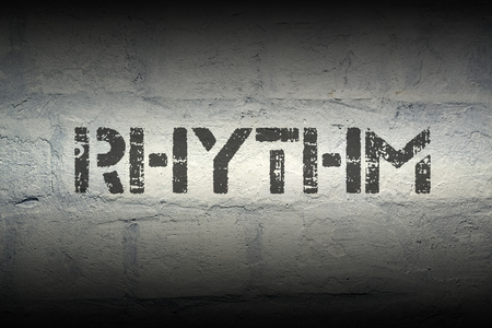 tempo: rhythm word stencil print on the grunge white brick wall
