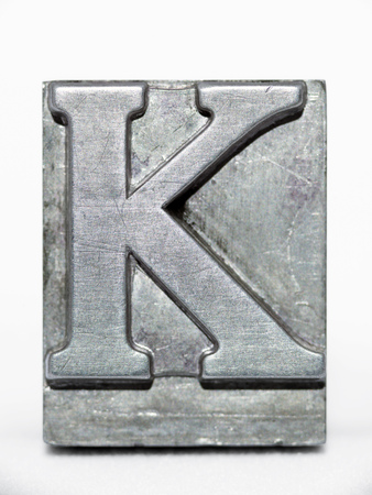 letter K metallic letterpress type block front view isolated on white