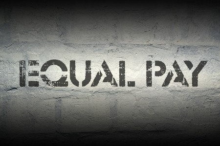 pay wall: equal pay stencil print on the grunge white brick wall Stock Photo