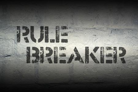 law breaker: rule breaker stencil print on the grunge white brick wall