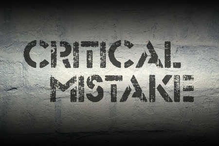 mistake: critical mistake  stencil print on the grunge white brick wall Stock Photo