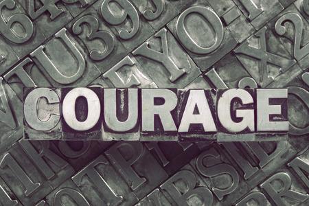 concetto di parola di coraggio fatto da blocchi di tipografia metallica su sfondo molte lettere