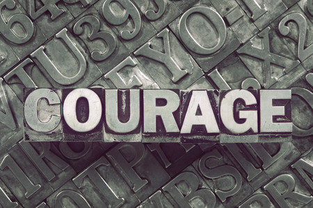courage word concept made from metallic letterpress blocks on many letters background