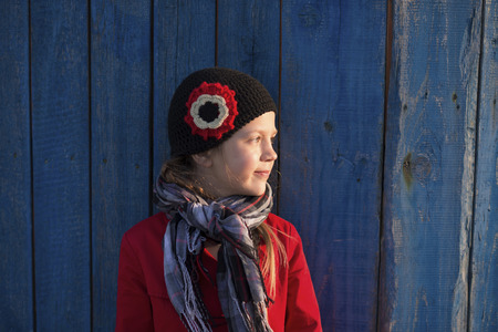 knitwear: girl in red raincoat and fashion knitwear cap near blue wooden fence by evening