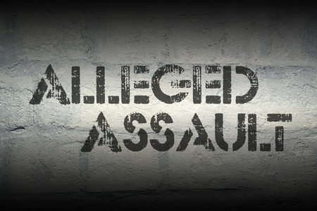 alleged: alleged assault stencil print on the grunge white brick wall Stock Photo
