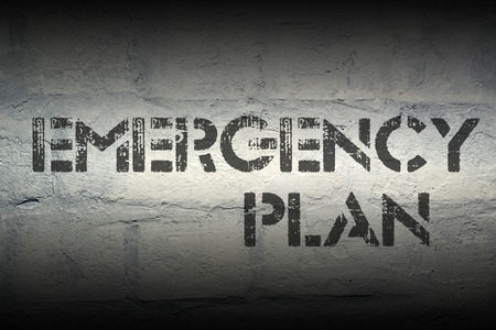emergency plan: emergency plan stencil print on the grunge white brick wall