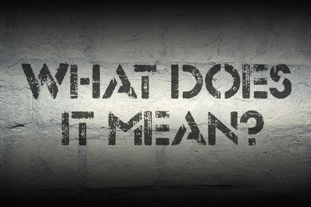 mean: what does it mean question stencil print on the grunge white brick wall