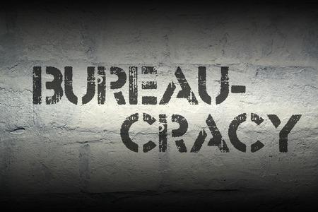 bureaucratism: bureaucracy word stencil print on the grunge white brick wall
