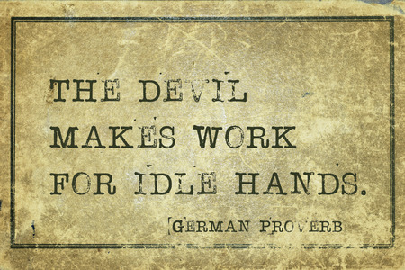 idle: The devil makes work for idle hands - ancient German proverb printed on grunge vintage cardboard Stock Photo