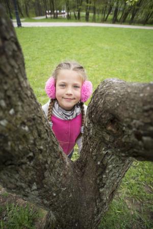 Earmuffs: girl in pink earmuffs hidden behind big tree Stock Photo