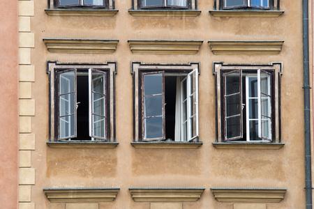 ventanas abiertas: vista frontal de la pared edificio antiguo con tres ventanas abiertas Foto de archivo