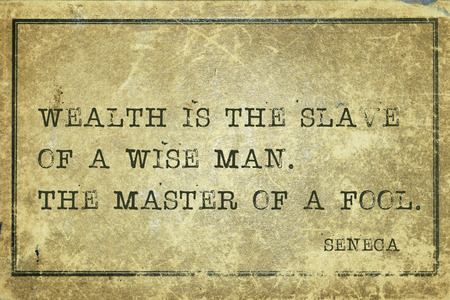 seneca: Wealth is the slave of a wise man - ancient Roman philosopher Seneca quote printed on grunge vintage cardboard Stock Photo