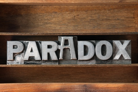 paradox: paradox word made from metallic letterpress type on wooden tray