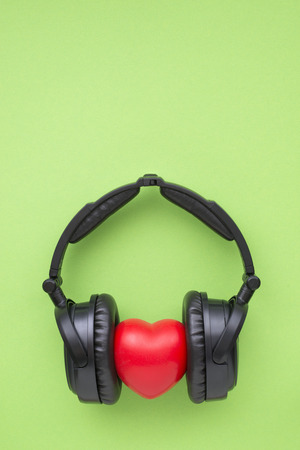 audiophile: black headphones with red heart on green background with blank space