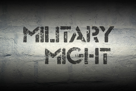 might: military might stencil print on the grunge white brick wall