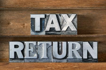 Steuererklärung aus metallischen Buchdruck auf hölzernem Tablett