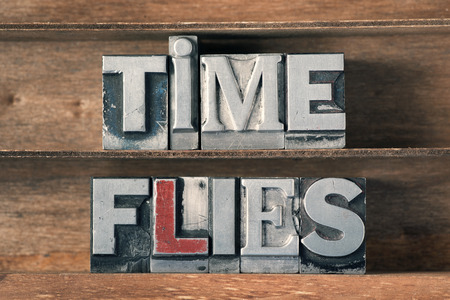 time flies: time flies phrase made from metallic letterpress type on wooden tray